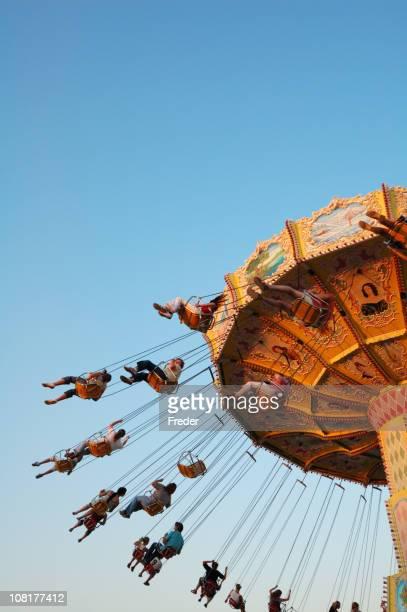 People Riding Swing Carousel