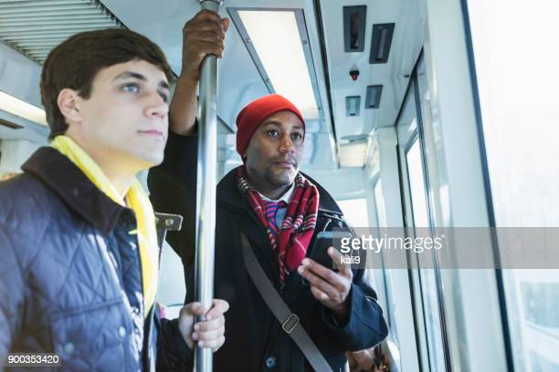 People riding train to work in winter using mobile phone