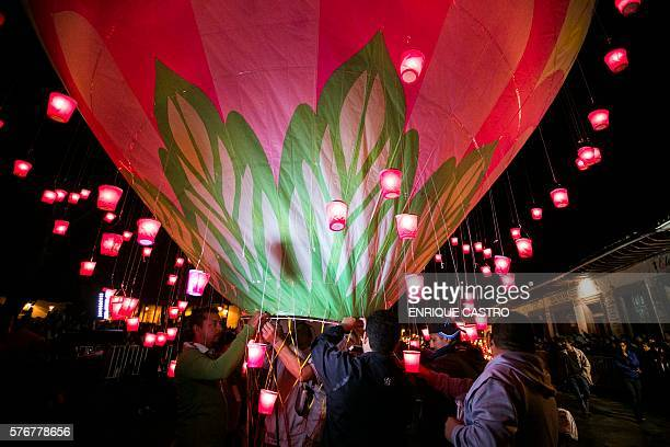 People rise balloons during the second day of the International Cantoya Festival in Patzcuaro Michoacan State Mexico on July 16 2016 / AFP / ENRIQUE...