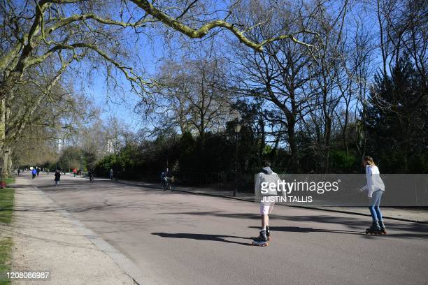 People rollerblade in Battersea Park in London on March 24 2020 after Britain's government ordered a lockdown to slow the spread of the novel...