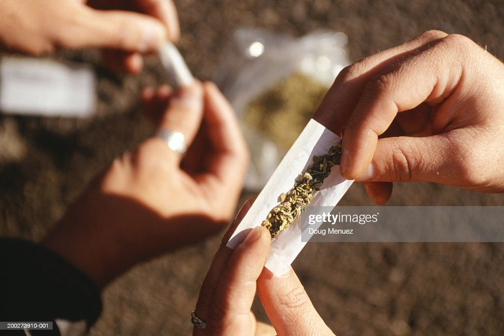 People rolling joints on street, close-up of hands : Stock Photo