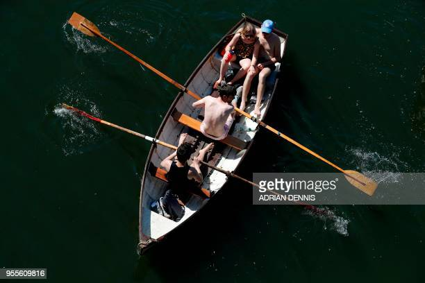 People row a boat along the River Thames as they soak up the sun in Richmond south west London on May 7 2018 Temperatures on Monday were predicted to...