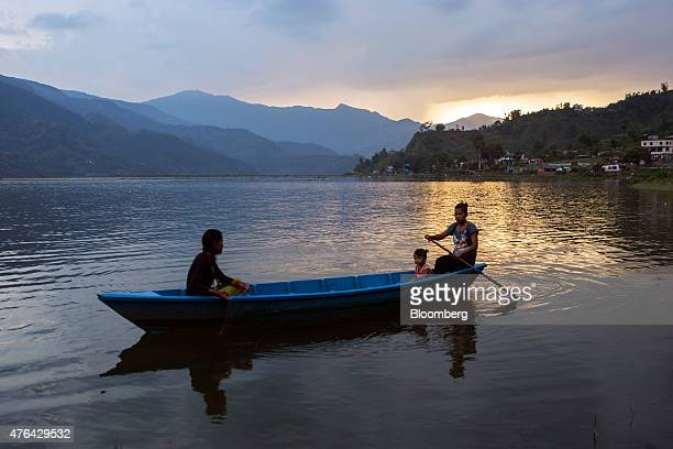 People row a boat as the sun sets over Phewa lake in Pokhara Nepal on Monday June 1 2015 Nepal's gross domestic product will probably grow 38% in the...