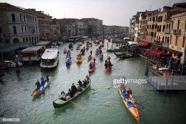 People row during the masquerade parade on Grand Canal during Venice Carnival on February 12 2017 in Venice / AFP PHOTO / Marco BERTORELLO