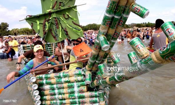 People row their vessel made of beer cans as thousands flock to Darwin's Mindal beach during the annual Darwin Beer Can Regatta July 29 2007 in...