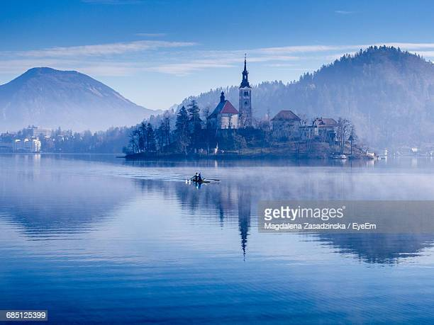 People Rowing Boat In Lake By Church And Mountains Against Sky During Foggy Weather