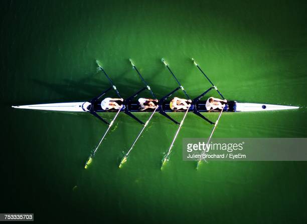 people rowing boat in water - a team stock photos and pictures