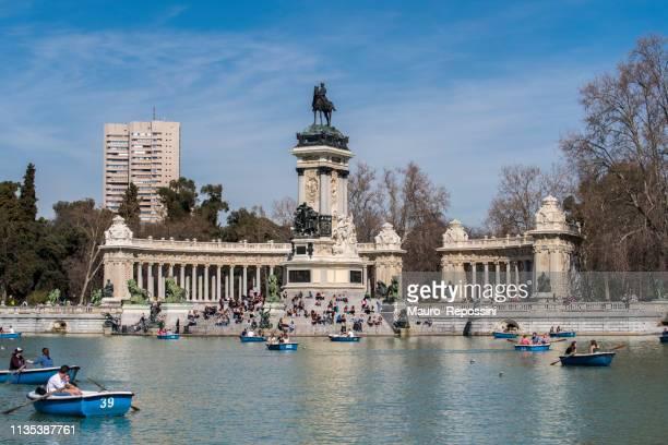 gente remando en el estanque junto al monumento a alfonso xii de españa, en el parque del retiro (parque del retiro) en la ciudad de madrid, españa. - alfonso fierro fotografías e imágenes de stock