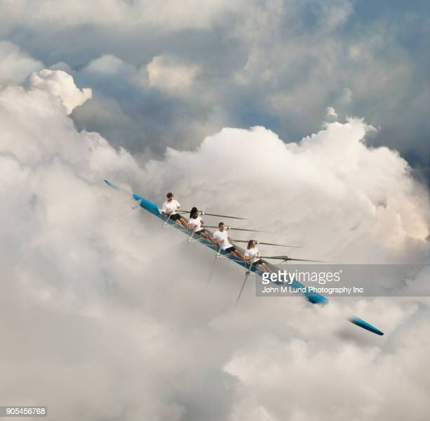People rowing kayak in the clouds
