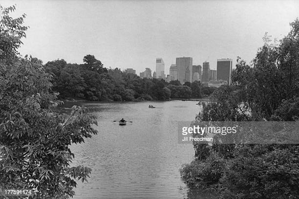 People rowing on Central Park Lake with the Manhattan skyline behind New York City circa 1980