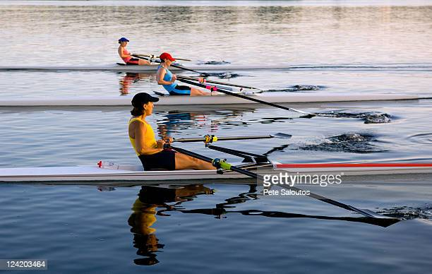 People rowing sculling boats on river