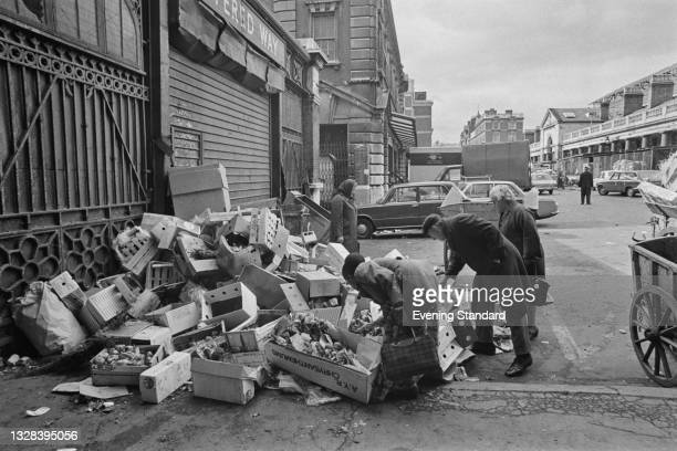 People rummage through discarded crates at Covent Garden fruit and vegetable market in London, UK, during its relocation to the New Covent Garden...