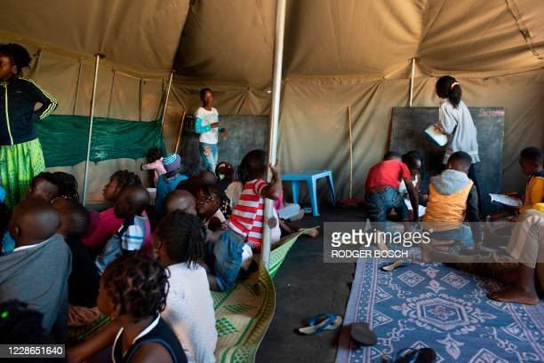 People run a makeshift school in a tent which is part of a group of about 630 people, refugees originally from Democratic Republic of Congo, Rwanda,...