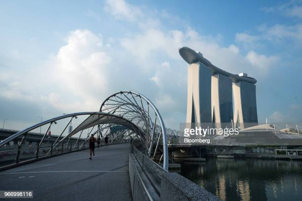 People run across a bridge in front of the Marina Bay Sands hotel and casino in Singapore, on Sunday, June 3, 2018. U.S. President Donald Trump and...
