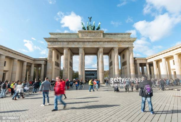 people run across the square at brandenburg gate, berlin, germany - mensch im hintergrund stock-fotos und bilder
