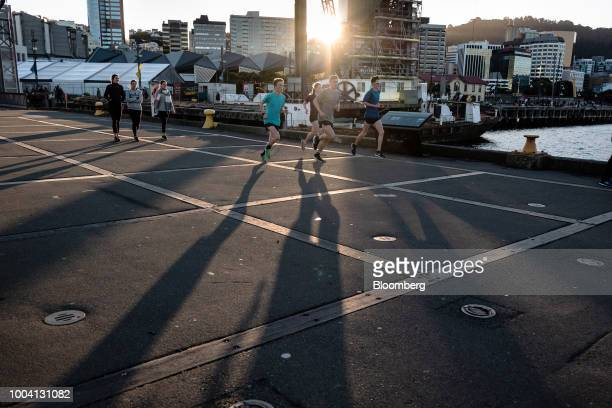 People run along a waterfront in Wellington New Zealand on Wednesday July 18 2018 New Zealand inflation picked up in the second quarter amid higher...
