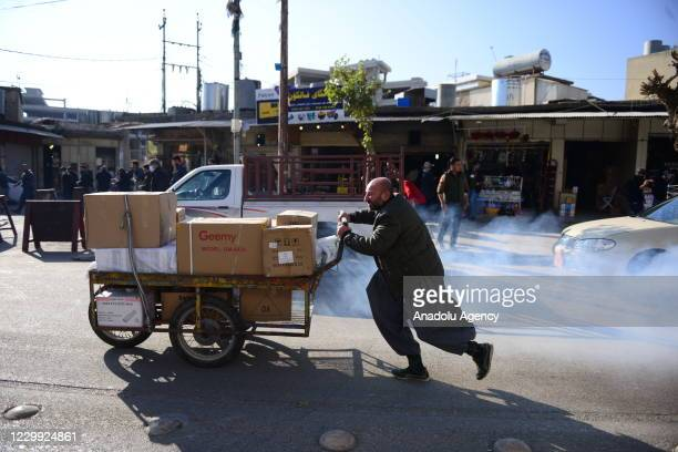 People run away as they are affected from tear gas thrown by security forces during a protest against salary delays at Mevlevi street in...