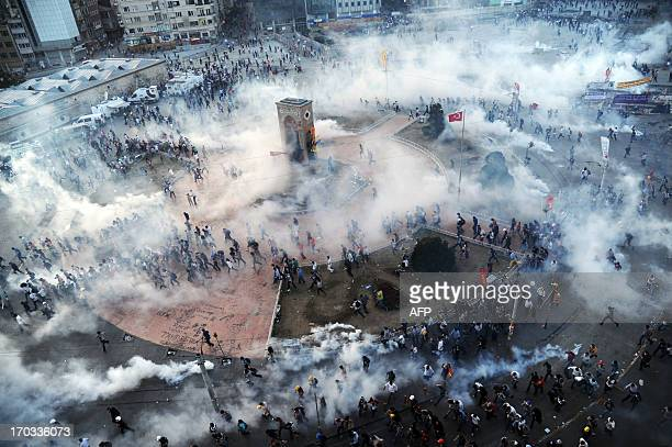 People run away as Turkish riot policemen fire tear gas on Taksim square on June 11 2013 Turkish police fired massive volleys of tear gas and jets of...