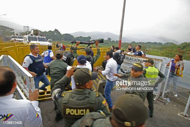 TOPSHOT People run away as two Venezuelan armor vehicles drive from the Venezuelan side of Simon Bolivar International Bridge towards Colombia in...