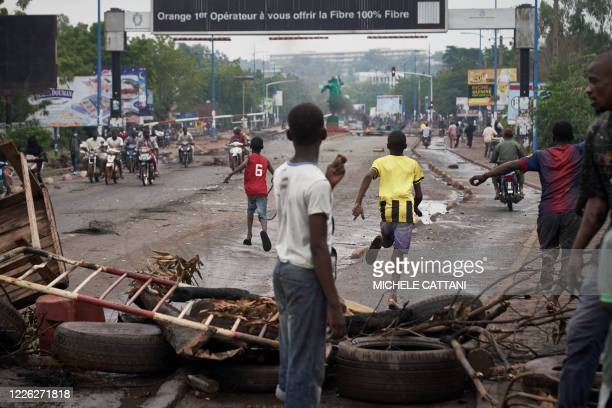 People run away at the arrival of the riot police as protesters set barricades to block the circulation on the Martyrs bridge of Bamako on July 11...