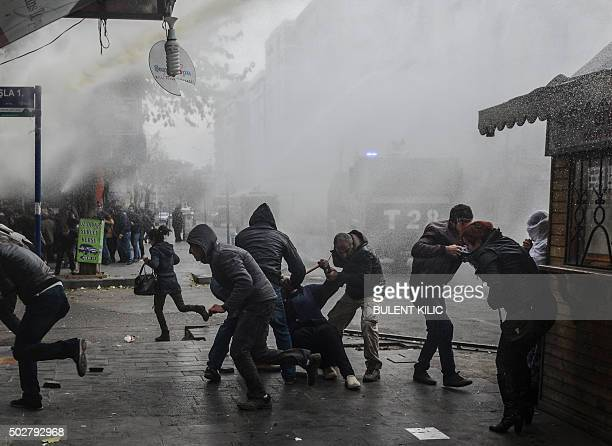 People run away from tear gas and water cannon as they protest against curfews on December 29 in Diyarbakir Turkish President Recep Tayyip Erdogan...