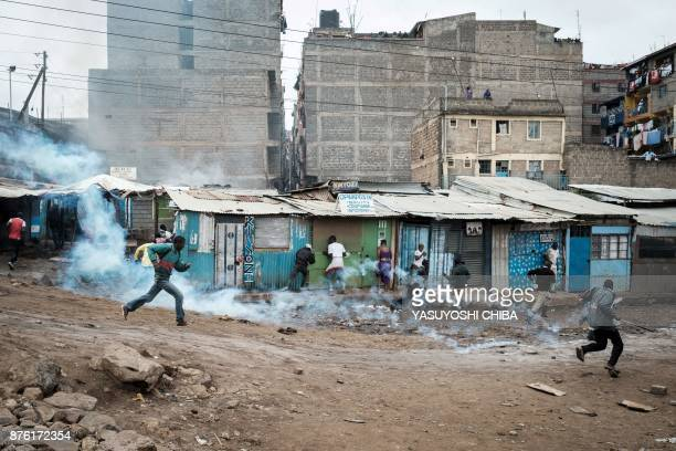 TOPSHOT People run away from tear gas before the arrival of Kenya's opposition party National Super Alliance leader at Riverside slum in Nairobi on...