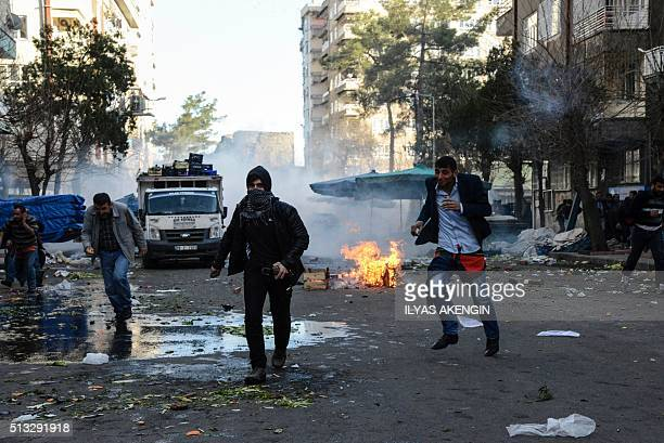 People run away from tear gas during clashes between Turkish forces and Kurdish people in the centre of Diyarbakir during a protest against a curfew...