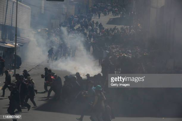People run away from the tear gas as antigovernment demonstrators clash with the police during a funeral procession of the victims killed during...