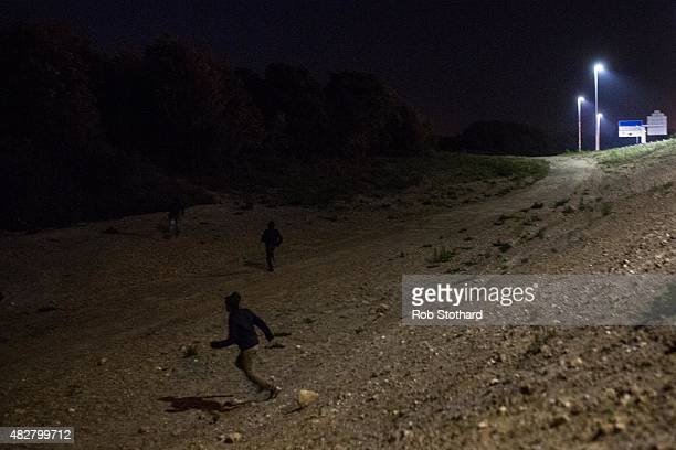 People run down a bank near the Eurotunnel terminal in Coquelles on August 3 2015 in Calais France Hundreds of migrants are continuing to attempt to...
