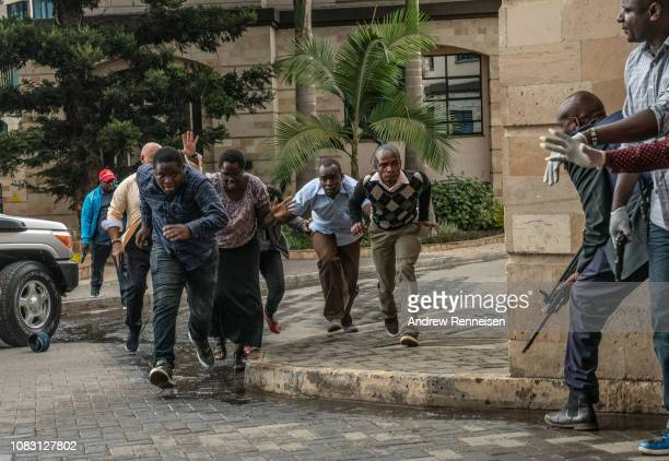 People run for cover after being rescued from the Dusit Hotel on January 15, 2018 in Nairobi, Kenya. A current security operation is underway after...