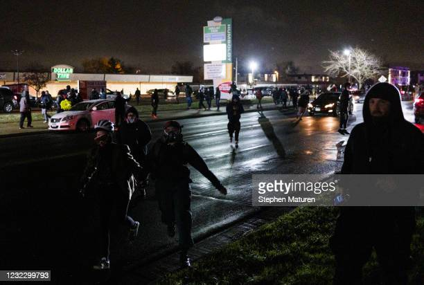 People run from law enforcement officers near the Brooklyn Center police headquarters on April 13, 2021 in Brooklyn Center, Minnesota. Demonstrations...