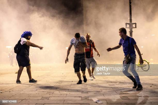 People run from tear gas as French football fans clash with police following celebrations around the Arc de Triomph after France's victory against...