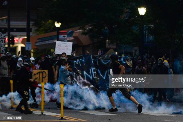 People run from tear gas as they march along Colfax Avenue during the fourth consecutive day of protests in the aftermath of the death of George...