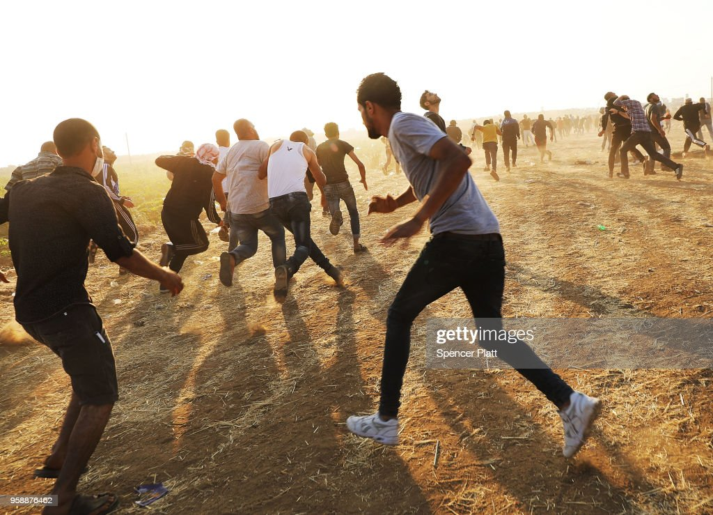 People run from tear gas at the border fence with Israel on May 15, 2018 in Gaza City, Gaza. Israeli soldiers killed over 50 Palestinians and wounded over a thousand as demonstrations on the Gaza-Israel border coincided with the controversial opening of the U.S. Embassy in Jerusalem yesterday. This marks the deadliest day of violence in Gaza since 2014. Gaza's Hamas rulers have vowed that the marches will continue until the decade-old Israeli blockade of the territory is lifted.