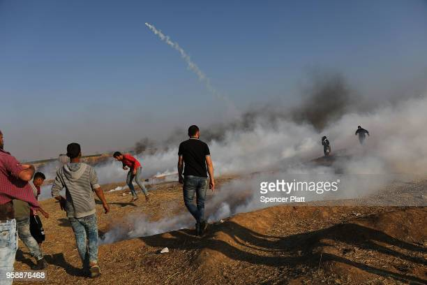 People run from tear gas at the border fence with Israel on May 15 2018 in Gaza City Gaza Israeli soldiers killed over 50 Palestinians and wounded...