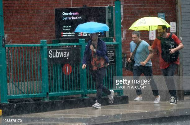 People run from the rain in the Chelsea area of New York on July 8, 2012 as Tropical Storm Elsa moves up the Northeast with heavy rain and flash...