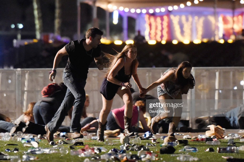 People run from the Route 91 Harvest country music festival after apparent gun fire was hear on October 1, 2017 in Las Vegas, Nevada. A gunman has opened fire on a music festival in Las Vegas, leaving at least 20 people dead and more than 100 injured. Police have confirmed that one suspect has been shot. The investigation is ongoing.