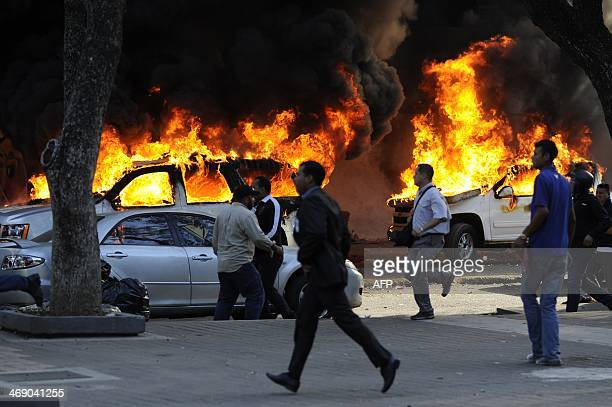 People run in front of burnt CICPC cars during an opposition demontration against the government of Venezuelan President Nicolas Maduro in Caracas on...