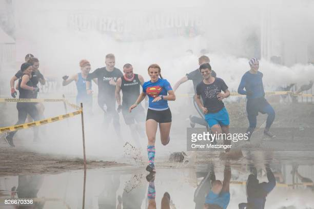 People run in muddy water as part of a race nicknamed 'Runmageddon' at the 2017 Woodstock Festival Poland on August 4 2017 in Kostrzyn Poland The...