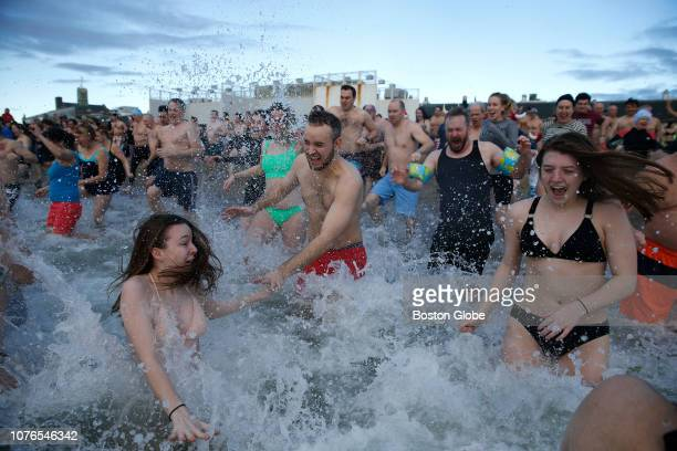 People run into the water during the L Street Brownies annual New Year polar plunge in South Boston on Jan 1 2019