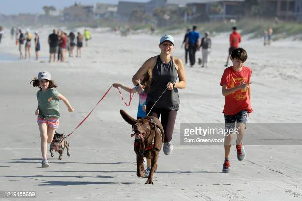 People run on the beach on April 17 2020 in Jacksonville Beach Florida Jacksonville Mayor Lenny Curry announced Thursday that Duval County's beaches...
