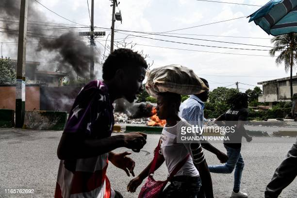 People run past burning tires during a protest against the fuel crises in Port-au-Prince, on September 2, 2019. - For more than a week, petroleum...