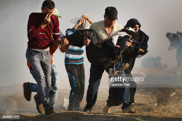People run through tear gas carrying an injured woman at the border fence with Israel on May 15 2018 in Gaza City Gaza Israeli soldiers killed over...