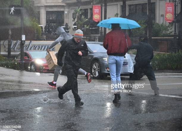 People run through water flooding a street in Glendale California on February 2 2019 Southern California is enduring three backtoback storms bringing...