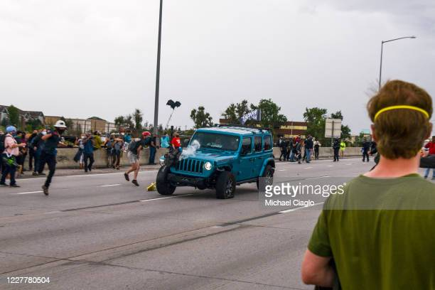 People run to get out of the way as a Jeep speeds through a crowd of people protesting the death of Elijah McClain on I225 on July 25 2020 in Aurora...