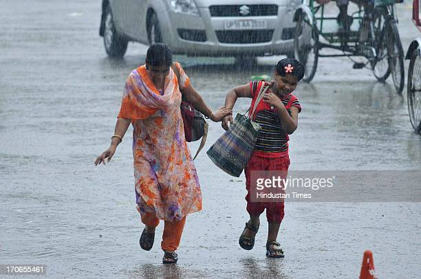 People run to take shelter during a heavy rainfall on June 16, 2013 in Noida, India. The national capital has been witnessing pre-monsoon showers,...