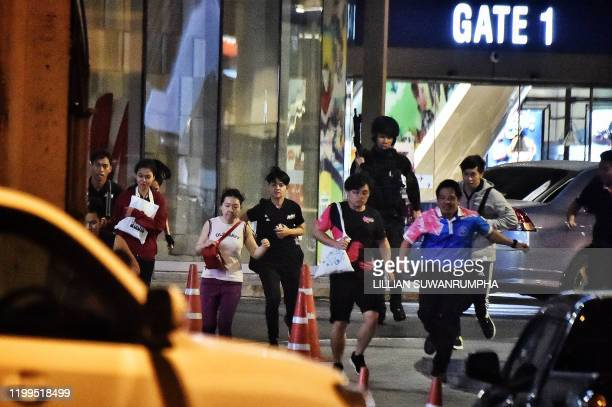 TOPSHOT People run together as they are rescued by Thai commandos from Terminal 21 shopping mall where a mass shooting took place on February 9 2020...