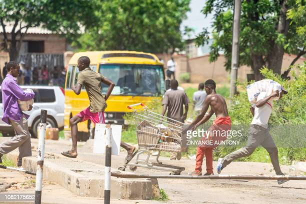 People run with loot from a local supermarket during as shutdown demonstration on January 14 2019 in Bulawayo after the president announced a more...