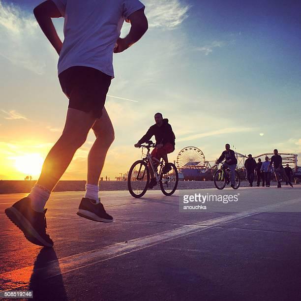 people running and cycling on the beach, santa monica, usa - santa monica stockfoto's en -beelden