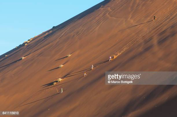 People running down the side of the famous Dune 45 sand dune. Sossuvlei, Namibia.